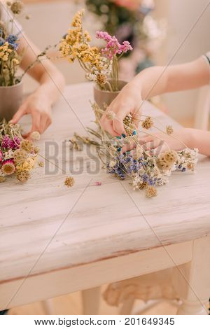 children make wreaths on a wooden table