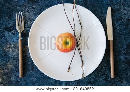 White Plate, Red Apple, Cutlery And Tree Brunches On A Blue Stone Background. Autumn, Thanksgiving,