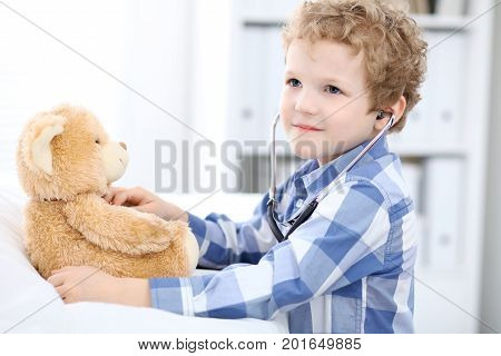 Child  patient afrer health exam playing as a doctor with stethoscope and teddy bear.