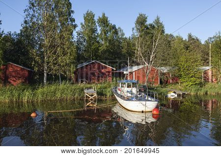 KOKKOLA, FINLAND ON JULY 07. View of a channel, a white boat and red wooden boathouses by the seaside on July 07, 2017 in Kokkola, Finland. Evening and bright sunshine. Editorial use.