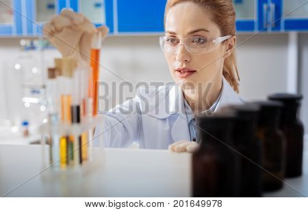 Positive thoughts. Beautiful young practitioner standing at her workplace and leaning on shelf while looking at test tube