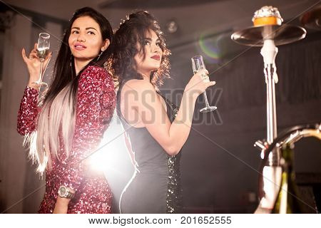 Beautiful girls posing with the glasses of wine or champagne in their hands. WOmen in shisha bar