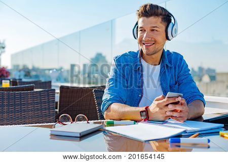 Meaningful song. Joyful young man looking into vacancy and dreaming while sitting on a terrace and listening to his favorite song alone.