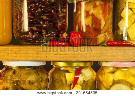 Jars with marinated food and organic raw vegetables. Preserved vegetables on wooden background. Various marinaded food. Life on a rural farm