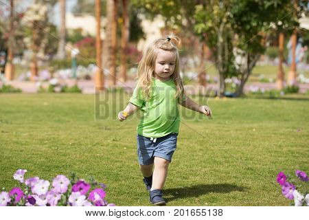 child with adorable happy face long blond hair wearing green shirt blue shorts running on meadow with pink flowers on background of trees in summer sunny day
