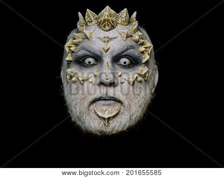 Monster face with scary look of white eyes. Alien or reptilian makeup with sharp thorns and warts. Demon head isolated on black. Horror and fantasy concept. Man with dragon skin and beard.