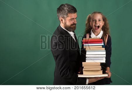Girl in school uniform and bearded man. Kid and dad hold huge pile of books. Home schooling and back to school concept. Father and schoolgirl with excited faces on dark green background copy space