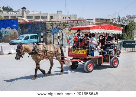 HEBRON ISRAEL - APRIL 12 2009: Undefined ultra orthodox jewish family on horse-drawn carriage at Hebron street
