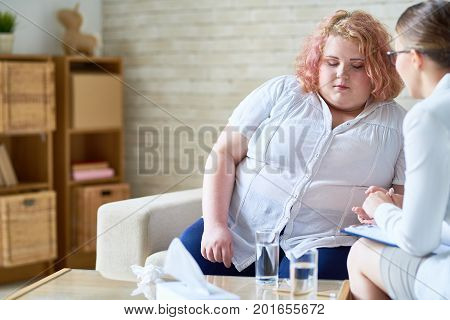 Portrait of female psychiatrist supporting obese young woman holding hands and comforting her during therapy session on mental issues
