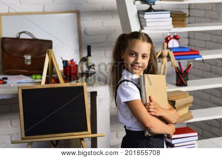 Back To School Concept. Schoolgirl Holds Book On Classroom Background