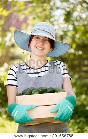 Photo of happy woman agronomist in hat with crop of cucumbers in box on background of trees