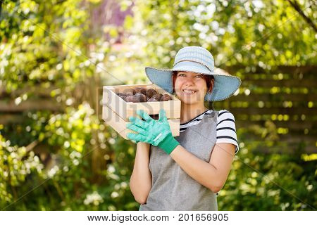 Young woman agronomist in hat with box of potatoes in summer