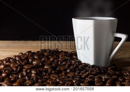 Low key coffee in the darkness. Roasted coffee beans on a wooden table with a glass of white ceramic.