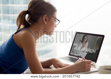 Jobless woman searching work opportunities online, looking on laptop screen, making notes, applying for new full or part time job, reviewing available open vacancies to submit resume on web, side view