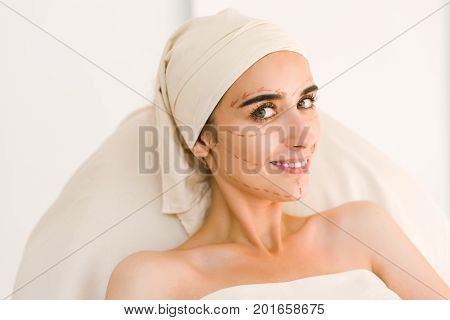 Attractive girl with dark eyebrows and naked shoulders at white background and looking at camera. Woman Smile.