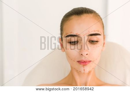 Correction lines on woman face. Before plastic surgery operetion. Attractive girl with dark eyebrows and naked shoulders at white background. Look down.