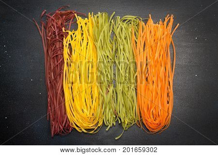 Overhead Of Traditional Italian Pasta Tagliatelle Of Different Colors On Dark Background. Raw Taglia
