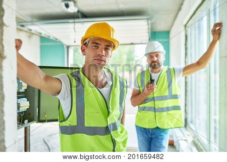Portrait of two professional builders wearing hardhats and reflective vests  posing confidently looking at camera inside of unfinished building
