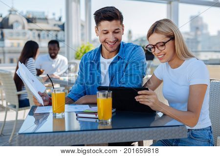 Always working in a team. Radiant young gentlean and lady in casual looking at a screen of a tablet computer and beaming while working on university assignment together.