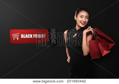 Happy Asian Woman Holding Paperbag With Black Friday Text