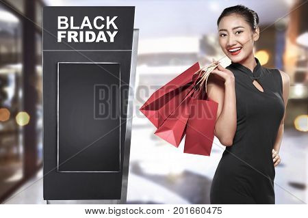 Cheerful Asian Woman With Paperbag Standing Beside Advertising Billboard