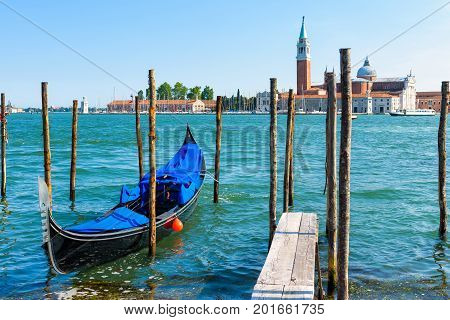 Pier with the gondola near Saint Mark`s Square in Venice, Italy. The gondola is a traditional romantic transport in Venice.