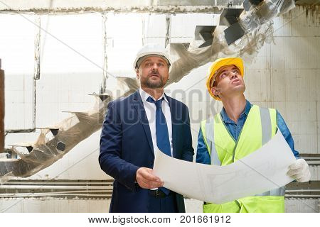 Portrait of foreman and supervisor discussing floor plans on site standing by unfinished flight of stairs