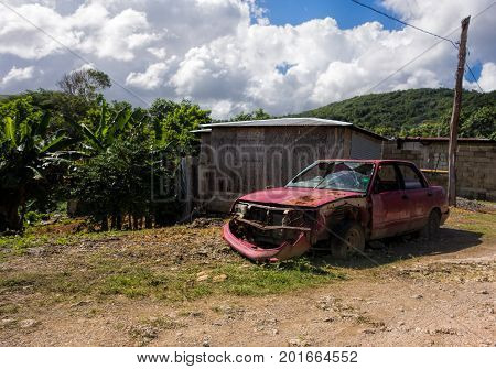 Broken and rusty car left abandoned in lush environment in the outskirts of Boston Bay in Portland parish Jamaica on 30 December 2013.