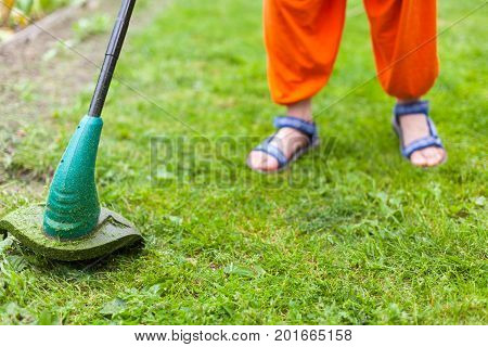 Gasoline lawn trimmer mows juicy green grass on a lawn on a sunny summer day. Close-up selective focus image. Garden equipment. Young woman mowing the grass with a trimmer.