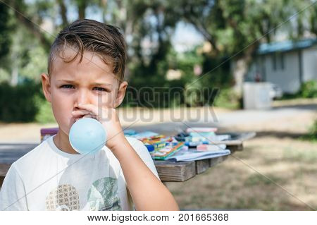 Portrait of schoolboy looking at camera and blowing up balloon on background of table with school supplies.