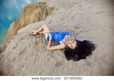 Woman In The Blue Swimsuit On The Sand At The Beach Near The Sea Lies In The Rays Of The Evening Sun