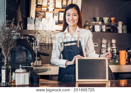 Asian female barista wear jean apron and holding blank blackboard menu at counter bar with smile facecafe service conceptowner business start upmock up for display of drink menu or text