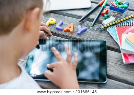 Anonymous kid posing with tablet and school supplies at table with word Play made of colorful letters.