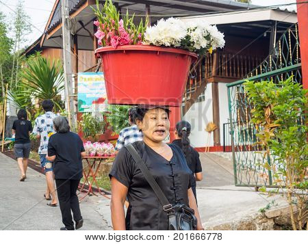 Sangkhlaburi Thailand- March 05 2017: The unidentified Mon woman selling flowers for tourists in Sangkhlaburi while showing her skill in holding flowers in the big red plastic container on her head.