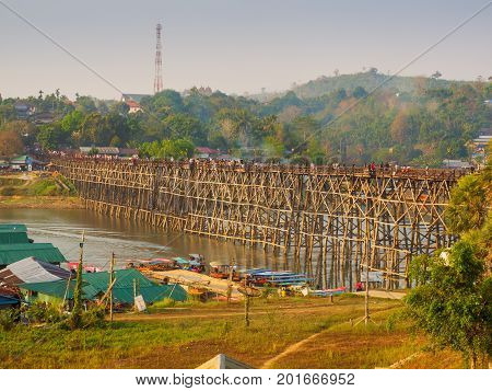 Sangkhlaburi Thailand - March 05 2017: The scenery of the Mon wooden bridge over the river in Sangkhlaburi District Kanchanaburi Province Thailand while tourists walking across the bridge on the morning of March 05 2017