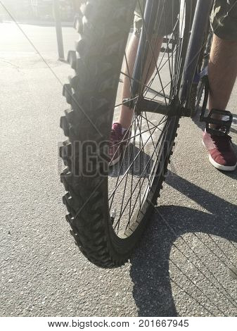 Close up of front bike wheel on asphalt and male legs