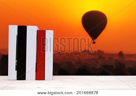 stack book on desk no labels blank spine with blurred image of silhouette of balloon at sunrise in the morning over Bagan in Myanmar education back to school history landscape nature concept