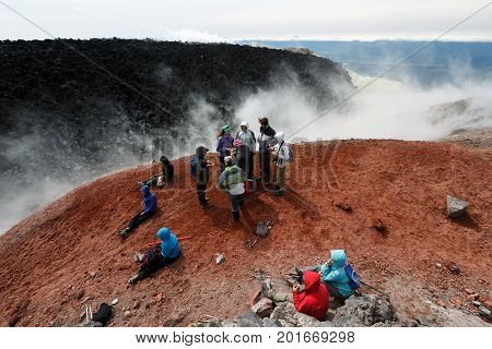 AVACHA VOLCANO KAMCHATKA PENINSULA RUSSIAN FAR EAST - AUG 7 2014: Large group of tourists and travelers rests in crater of active Avachinsky Volcano after hours of climbing to the top of volcano.