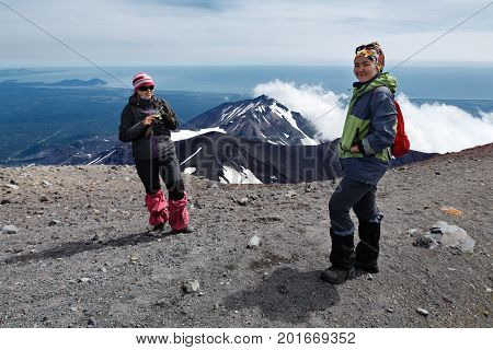 AVACHA VOLCANO KAMCHATKA PENINSULA RUSSIA - AUG 7 2014: Two young women tourists stand of top of crater of active Avachinsky Volcano on background of cone of Kozelsky Volcano and Pacific Ocean.