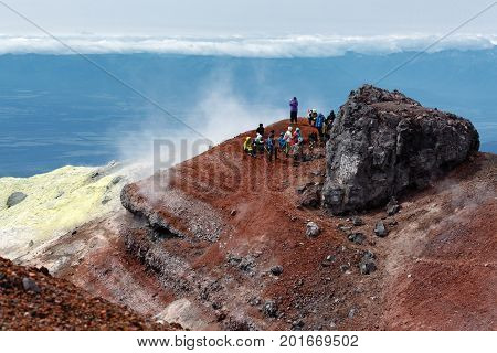 AVACHINSKY VOLCANO KAMCHATKA PENINSULA RUSSIAN FAR EAST - AUG 7 2014: Large group of tourists and travelers rests in summit crater of active Avacha Volcano after climbing to the top of volcano.