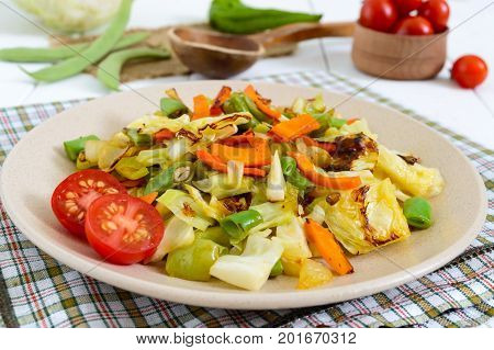 Vegetable stew - a mixture of baked cabbage green beans onions carrots cherry tomatoes sweet pepper on a plate on a white wooden background. Vegan cuisine. Proper nutrition.