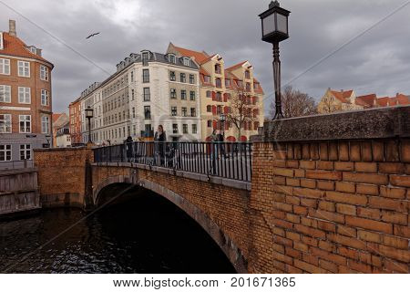 COPENHAGEN, DENMARK - NOVEMBER 7, 2016: People walking on Snorrebro bridge across Chrisianshavn canal. The canal is noted for its bustling sailing community with numerous house- and sailboats