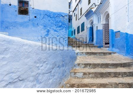 Detail of a narrow street in the mountain town of Chefchaouen with blue buildings in Morocco; Concept for travel in Morocco