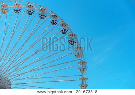 Ferris wheel on blue sky background. In the amusement Park. The weekend