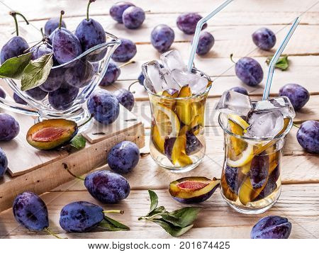 Refreshing drink from fresh juicy sweet sips with lemon in glass mugs with ice cubes on a wooden background with plums and green leaves with plums in a glass sauceboat