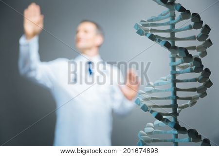 Implementing ideas. Close up of a demonstrational dna model standing in front of a shot with a mature medical professional touching an invisible screen while working alone.