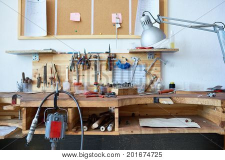 Background image of wooden workstation table in jewelers workshop with tools on it