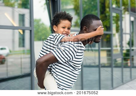 side view of young african american father piggybacking cute smiling son