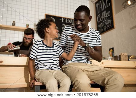 happy father and son holding hands and smiling each other while sitting on stools in cafe