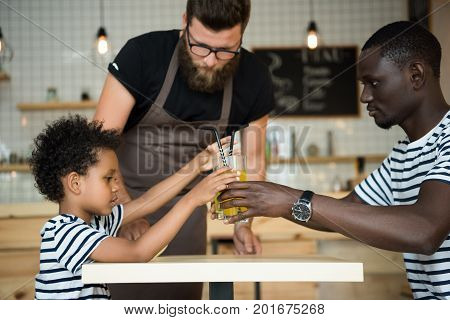 bearded waiter in eyeglasses standing near african american father and son drinking lemonade in cafe